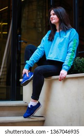 Livestyle portrait of a brunette girl in a blue dwarf toe on the streets of the city of Lvov.Ukraine