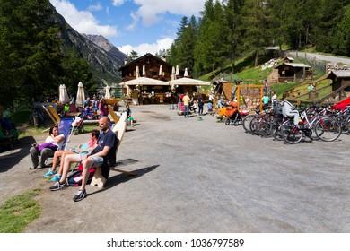 LIVIGNO, ITALY - AUGUST 1: People sunbathing in front of restaurant with playing kids and bikes on bank of Lago di Livigno on 1 August 2016 in Livigno, Italy.