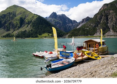LIVIGNO, ITALY - AUGUST 1: Woman on wooden pier with boats, kayaks and pedal boats on Lago di Livigno on 1 August 2016 in Livigno, Italy.
