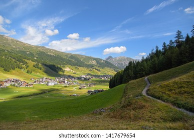 Livigno / Italy, August 20, 2016: a beautiful summer scene from Livigno, hiking trough the pine forest and the green meadow, travel photography, alpine landscape