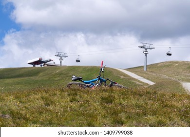 LIVIGNO, ITALY - AUGUST 4 2016: Full suspension downhill mountain bike lying on ground, mountains over Livigno with cableway in background on 4 August 2016 in Livigno, Italy.