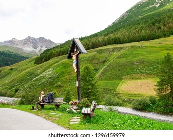 Livigno, Italy - July 21, 2017: Wooden crucifix near a mountain path