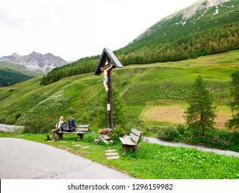 Livigno, Italy - July 21, 2017: Wooden crucifix near a mountain path