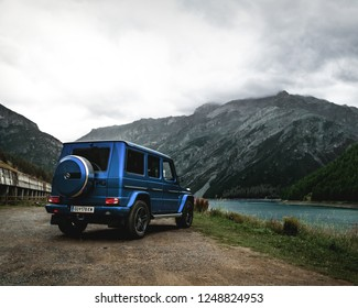 Livigno, Sondrio / Italy -  08.13.2018: Great adventure in the dolomites with a G500 where we stopped in the nature. Mountains, Lake and the G Class in the background. Livigno G-Class