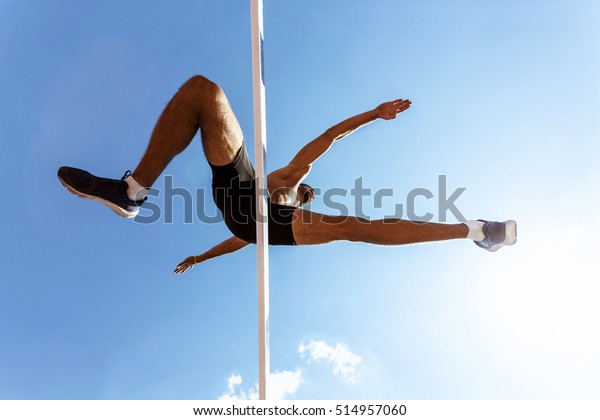 Living actively. Low angle shot of a muscular male athlete jumping over hurdle while running track and field race on a hot sunny day blue sky on the background
