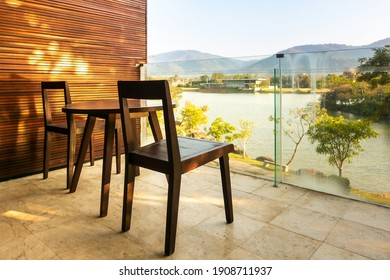 Living area on the balcony with wooden chairs and table
