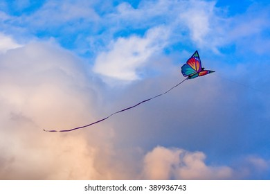 """""""Living in the clouds"""": Butterfly shaped kite in the cloudy sky"""