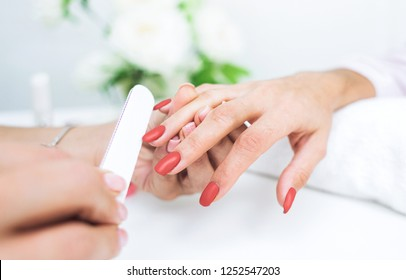 living coral 2019 color of the year. Young woman getting manicure in beauty salon. Close-up