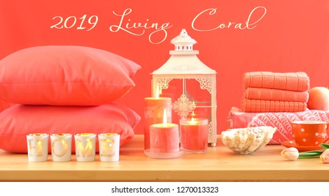 Living Coral 2019 Color of the Year homewares table setting with candles, towels, and throw cushions decor, with text.