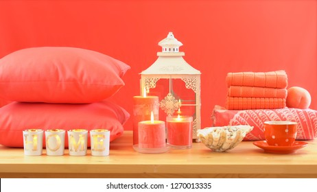 Living Coral 2019 Color of the Year homewares table setting with candles, towels, and throw cushions decor.