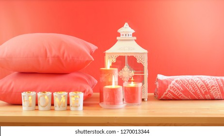 Living Coral 2019 Color of the Year homewares table setting with candles, towels, and throw cushions decor, with lens flare