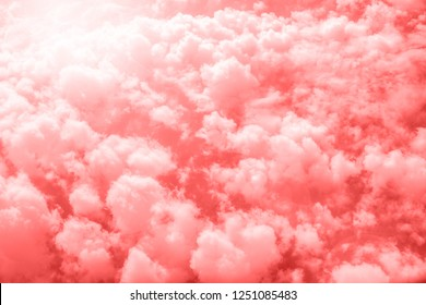 Living Coral color of the Year 2019. Aerial view of sky with fluffy clouds. Retro toned abstract background.