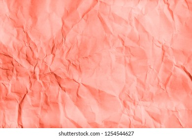 Living Coral Crumpled paper texture. Creative concept of color of the year 2019 16-1546. Flat lay, top view.