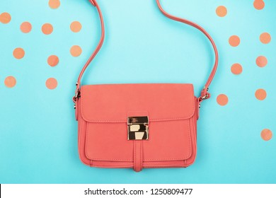 Living coral fashion bag and confetti on contrast background. Trendy color of 2019 year concept. Flat-lay, top view. Copy space for your text.