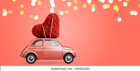 Living coral retro toy car delivering craft heart for Valentine's day on coral background