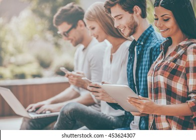 Living in digital age. Group of happy young people holding different digital devices and smiling while sitting in a row outdoors