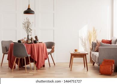 Sala y comedor interior con sofá gris y mesa cubierta de manteles naranjas