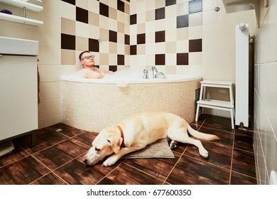 Living with dog. Young man relaxing in bathroom with his yellow labrador retriever.