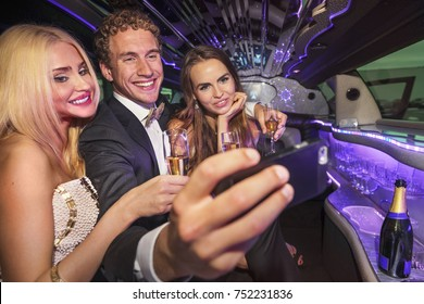 Living the glamourous life, drinking champagne in a limousine an taking a selfie