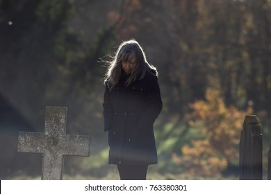 Living with grief and mortality. Thinking lady mourns at old grave cross in cemetery. Sadness at death and mortality by middle-aged to elderly woman dressed in black with head bowed.