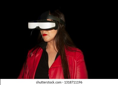 Living immersive reality in Mexico woman analytically  with special glasses observes what the glasses show, she wears long brown hair red jacket and red lips