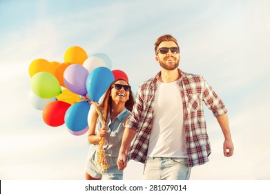 Living life to the fullest. Cheerful young couple holding hands and smiling while walking outdoors with colorful balloons