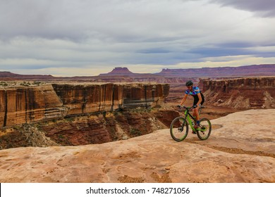 Living on the Edge: a man rides his bike along the canyon cliff in Canyonlands National Park, Utah, USA