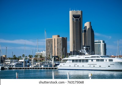 Living on the water Corpus Christi , Texas with Large massive Yatch in front of Downtown skyline cityscape of Bayfront Marina