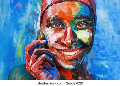 Living painting - smiling woman completely covered with thick paint