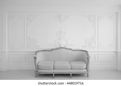 Living room with antique stylish light sofa on luxury white wall design bas-relief stucco mouldings roccoco elements. Black and white photo.