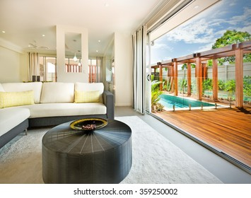 Living room with a beautiful outside view of house and pool with wooden floor