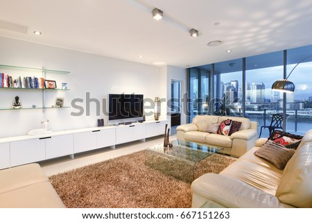 Living Room With Books Near Television, Comfortable Furniture And Designs,  Walls Are White Color
