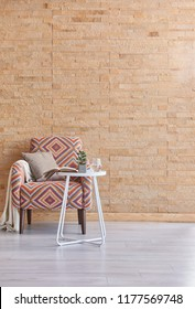 Living room brick wall background furniture decoration. Colorful armchair with blanket style. Decorative frame detail.