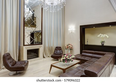 Living room in brown, beige colors with fireplace and big mirror over, leather sofa and armchairs around. Lighting room with big windows, and flowers on table.