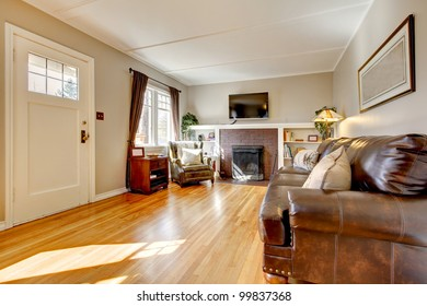 Living room with brown curtain and hardwood floor and leather sofa.