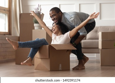 In living room cheerful african wife raised hands feels excited sit inside carton box husband rides her family celebrate moving day ready for relocation at new home first dwelling modern house concept