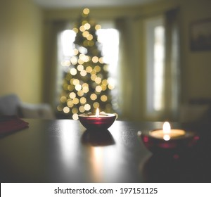 A living room at Christmas with a tree and burning candles.