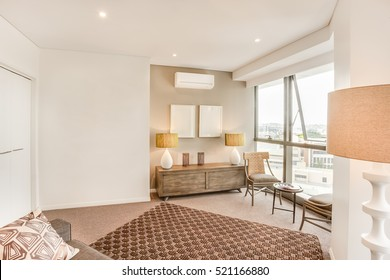 Living room with city view near glass windows, sofa set including pillows, lamps on the wooden table, walls are white color, floor carpet has some designs, daytime scene also perfect lightning.