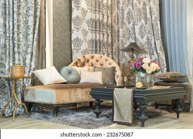 living room with classic looking sofa, luxury curtains, lamp and glass table