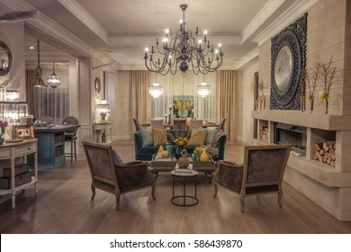 Living room in classic style with luxury and Provence, with a blue sofa and brown armchairs, a fireplace, a large wrought clocks, chandeliers and decorative elements