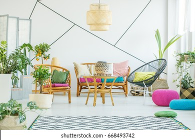Living room with colorful poufs, plants and decorative tape on the wall
