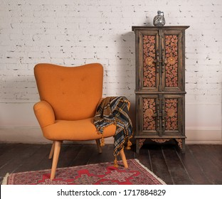 Living room corner with french orange wingback armchair, decorated wooden cupboard, on white bricks wall and grunge wooden parquet with red decorated carpet