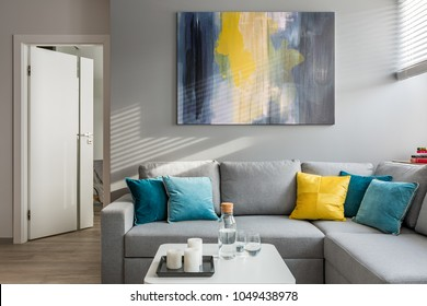 Living room with corner sofa, colorful cushions and white coffee table