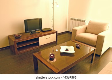 Living room with cosy sofa and arm chair, small table and DVD and TV set.