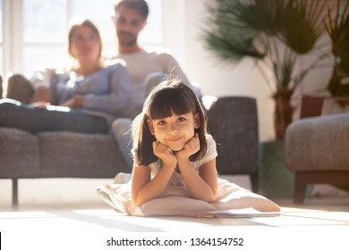 In living room couple resting on couch focus on adorable cute daughter kid look at camera lying on cushion pillow warm wooden floor. Lazy weekend free time, new modern cozy home, loan mortgage concept