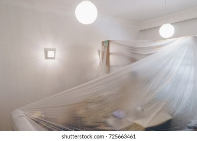 Living room is covered with protective plastic sheet, preparing for painting