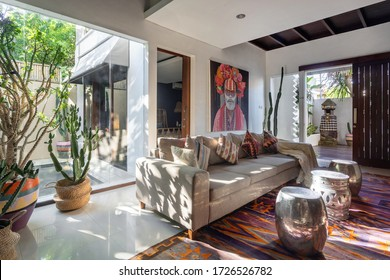 Living room in cozy house with stylish interior, ethnic decor, cushions on comfortable couch, woven ornamental carpet, cactus in wicker basket and artwork on wall