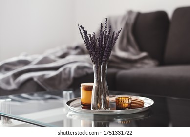 Living room decor: glass coffee table with dried lavender bouquet and aroma candles on a metal tray, sofa and blanket on background. Scandinavian style. Simple home decoration