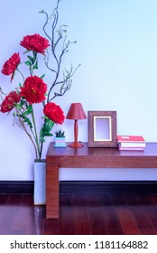 Living room decoration with colorful artificial flower, lamp & photo frame on wooden table / Home improvement design concept
