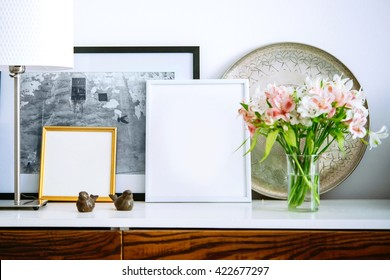 Living room decoration. Framed pictures, flowers and lamp on wooden console